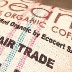Photo of burlap bag of Coffee beans. Text on the bag says, 100% Organic Coffee. Certified Organic by Ecocert SA. Fair Trade.