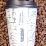 Photo of compostable coffee cup on a background of coffee beans.